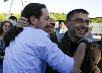 Podemos (We Can) leader Pablo Iglesias embraces former Podemos party member Juan Carlos Monedero during the closing campaign rally in Madrid