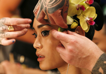 Orchids are attached to a model's hair backstage at the Issa Spring/Summer 2013 collection at London Fashion Week