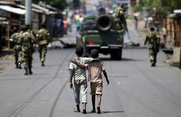 Boys walk behind patrolling soldiers in Bujumbura