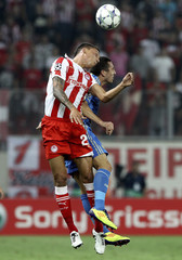 Marseille's Amalfitano and Holebas of Olympiakos jump for a header during their Champions League Group F soccer match in Piraeus near Athens
