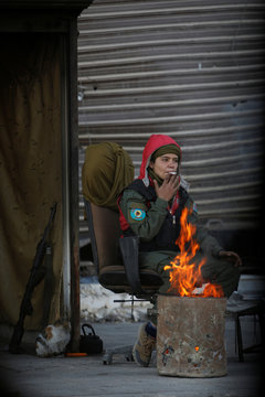 A Kurdish female fighter smokes a cigarette as she sits at the entrance of Bustan al-Basha area in Aleppo