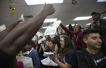 Activists chant inside a McDonald's restaurant in Los Angeles, California during a protest demanding better wages for fast-food workers