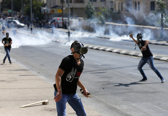 Palestinian protester throws stones at Israeli troops during clashes at a protest against the Israeli offensive in Gaza, in the West Bank town of Bethlehem