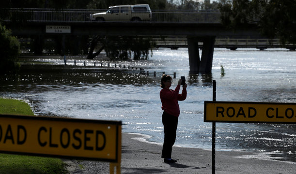 A woman takes a picture of the flooded Forbes Lake after heavy rain created a declared natural disaster zone in the midwestern New South Wales town of Forbes