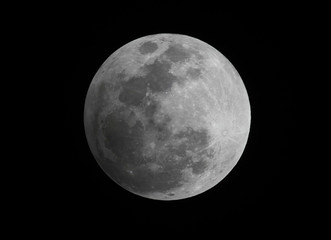 A penumbral eclipse of the moon is seen in the night sky in Manila