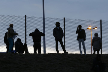Migrants are seen in silhouette as they stand on a rise near a fence as they gather near the Channel Tunnel in Frethun, near Calais