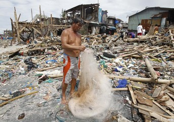 A man checks for fish in a net at a shanty area which was wiped out by strong currents brought by Typhoons Nesat and Nalgae in village of Tangos