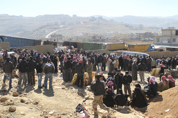 Syrian refugees who fled the violence from the Qalamoun area stand as they receive humanitarian aid from the Danish Refugee Council at the Lebanese border town of Arsal, in the eastern Bekaa Valley