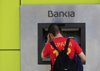 A man uses an ATM machine at a Bankia bank branch in the Andalusian capital of Seville
