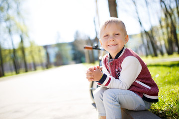 Boy sits on road afternoon