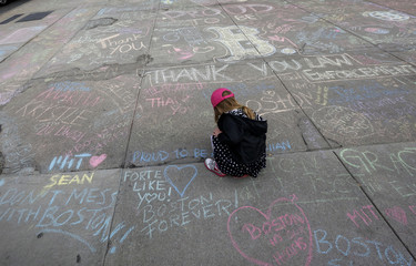 Jane Cosmas, 4-years-old, draws a heart amidst hundreds of chalk messages written by passersby about the Boston Marathon bombings on Newbury Street near the scene of the blasts in Boston