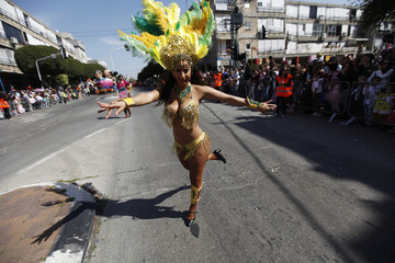 A woman dressed as a samba dancer performs during a parade celebrating the Jewish holiday of Purim near Tel Aviv