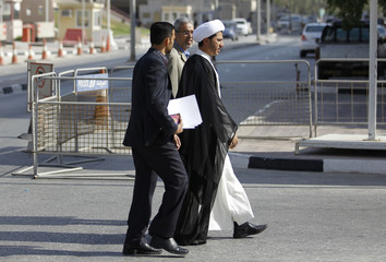 Wefaq Secretary General Sheikh Ali Salman, flanked by his bodyguard and his lawyer, arrives at the public prosecutor's office in Manama