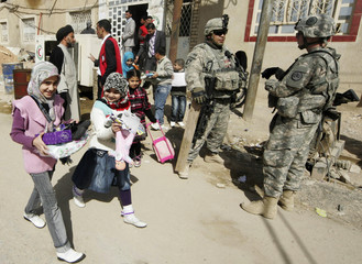 Girls carry stationary and toys as they pass U.S. soldiers standing guard near the Red Crescent association building in Kerbala, southwest of Baghdad