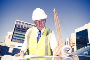 Senior foreman in glasses doing his job at building area on car