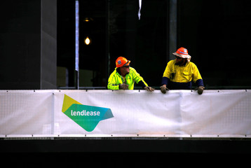 Construction workers lean on a fence adorned with a sign for the construction company Lendlease at a construction site in central Sydney, Australia