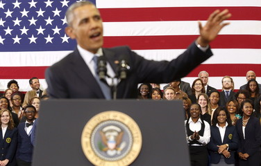 Students smile in the background as Obama delivers remarks on the economy at Lawson State Community College in Birmingham, Alabama