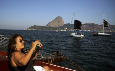 "Woman takes photos of black flags that are displayed on sailboats, as part of the installation ""Horizonte Negro"" (Black Horizon), during a protest in the Guanabara bay in Rio de Janeiro"