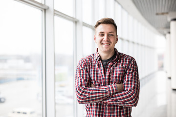 Portrait of smiling man standing with hands crossed in modern building