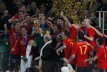 South Africa's President Zuma and FIFA President Blatter hand the World Cup trophy to Spain's team captain Casillas during the award ceremony at Soccer City stadium in Johannesburg