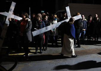 Actors portraying Jesus Christ hold crosses as they perform during Streetwise Opera's production of The Passion in Manchester