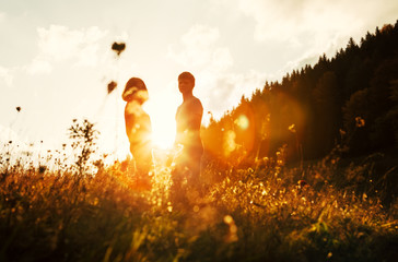 Young in love couple stay on meadow in bright sunset light