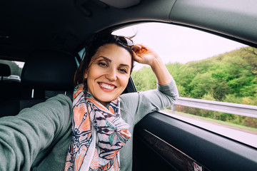 Happy smiling woman sits in auto