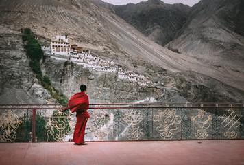Buddhist Monk in red robe looks on Diskit Monastery, Indian Himalaya, Nubra Valley