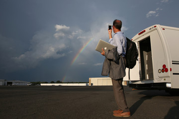 A media member covering Republican presidential candidate Donald Trump takes a photo of a rainbow on the tarmac in Charlotte