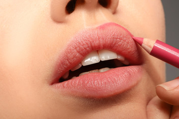 Lips of beautiful young woman applying makeup, closeup