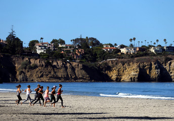 A group of women run together as they workout on the beach in La Jolla, California