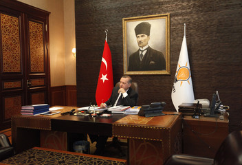 Turkey's PM Erdogan, with a portrait of modern Turkey's founder Ataturk in the background, watches television at his office at the AK Party headquarters in Ankara
