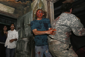 "A guest made up to look scary in fake blood reacts to an actor at the ""13th Floor"" haunted house in Denver"
