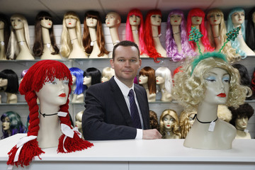 Director of Smiffys, Elliott Peckett, poses by fancy dress wigs their facility in Gainsborough