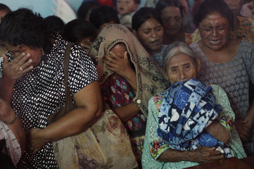 Women react during a mass for the skeletons of six people who disappeared during the internal armed conflict, at a church in the village of Pambach