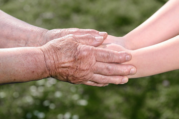 Old and young holding hands