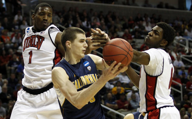 California's Kravish grabs a rebound against UNLV's Thomas and Marshall during their NCAA basketball tournament second round game in San Jose