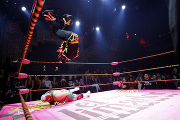 A lucha libre wrestler of The Crazy Chickens leaps in midair while fighting against Dr. Maldad during the Lucha VaVOOM show at the Mayan Theatre in Los Angeles