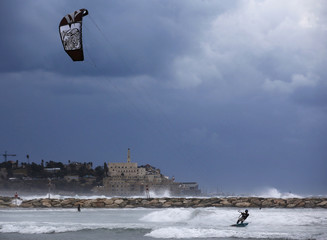 A man kite surfs in the Mediterranean sea in Tel Aviv, as the port of Jaffa is seen in the background