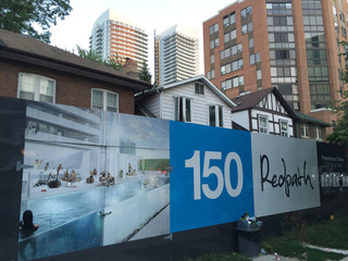 File photo of billboards surrounding a row of houses set to be demolished to make way for a condominium development feeding the real estate market of Toronto