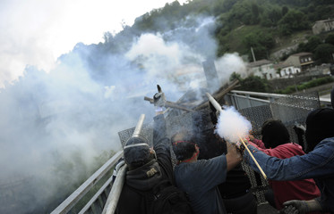 """Coal miners fire rockets during a clash with Spanish national riot police in the surroundings of the """"El Soton"""" coal mine in El Entrego"""