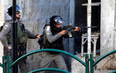 Israeli border policeman aims his weapon towards Palestinian protesters during clashes in the West Bank city of Hebron