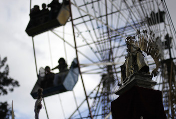 A procession of La Senora del Carmen passes by a ferris wheel in Guatemala City