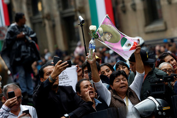 A fan holds a flag with a picture of the late Mexican singer Juan Gabriel during his official tribute outside Bellas Artes Palace in Mexico City, Mexico
