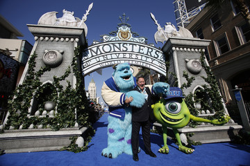 "Lasseter, Chief Creative Officer at Pixar and Walt Disney animation studios, poses with life-size characters of Mike and Sullivan at the premiere of the film ""Monsters University"" at El Capitan theatre in Hollywood"
