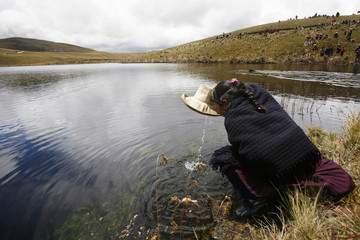 An Andean woman drinks water from the Cortada lagoon during a protest against Newmont's proposed Conga gold mine in the Andean region of Cajamarca
