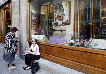 Two women talk each to other as a picture of Pope Benedict XVI is seen at an ice-cream shop in downtown Arezzo