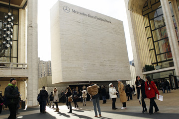 Pedestrians walk in front of the entrance to Fashion Week in Lincoln Center during New York Fashion Week
