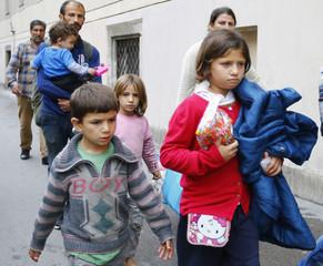 Migrant children walk down the street from Keleti train station in Budapest