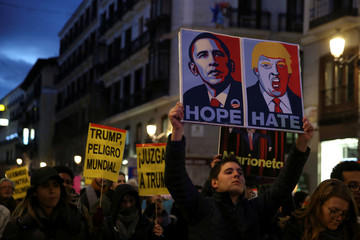 Demonstrators hold placards during a protest against U.S. President Donald Trump in Madrid